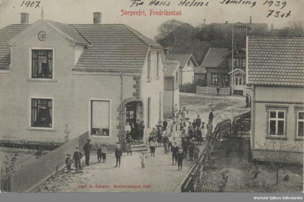 """Gateparti fra Sorgenfri 1905. Murbygning som ser ut til å ha en hjørnebutikk, skilt som ser ut som """"Skallebakke (?)"""". Masse barn på utsiden av butikken. Postkort. Butikken på bildet er idag Lurvelegg barnehage som ligger i Galtungveien på Sorgenfri. I bakgrunnen skimtes gamle Sorgenfri gård. Husene ved veien bak er til venstre Bruksgata 6. Huset med flaggstangen ved siden av er Bruksgata 4."""